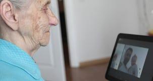 有灰色头发的一名年长妇女看在一种电子片剂的照片 影视素材