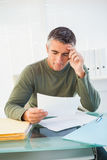 有灰色头发读书纸的微笑的人 免版税库存照片