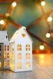 有灼烧的光里面的一点玩具圣诞节房子在blured绿色背景 库存图片