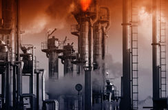 有灼烧的安全火焰和红色天空的炼油厂 免版税库存照片