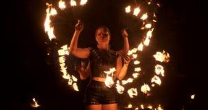 有灼烧的箍的三名妇女跳舞与在皮革衣裳的火热的火炬在展示马戏火的一个黑暗的飞机棚 股票录像