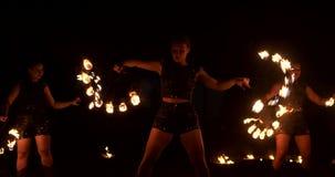 有灼烧的箍的三名妇女跳舞与在皮革衣裳的火热的火炬在展示马戏火的一个黑暗的飞机棚 股票视频