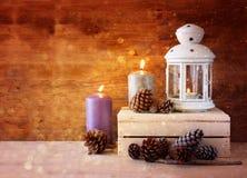 有灼烧的蜡烛、杉木锥体在木桌上和闪烁光背景的白色葡萄酒灯笼 被过滤的图象 免版税库存图片