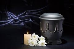 有灼烧的蜡烛白色菊花的黑公墓缸在深刻的蓝色背景 库存图片