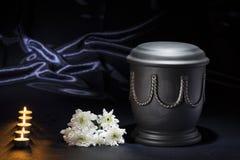 有灼烧的蜡烛白色菊花的黑公墓缸在深刻的蓝色背景 免版税库存图片