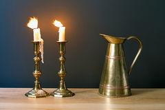 有灼烧的蜡烛的大烛台和在内部的古色古香的瓶子 图库摄影