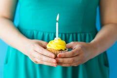 有灼烧的蜡烛的妇女在生日杯形蛋糕 图库摄影