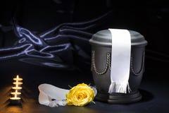 有灼烧的蜡烛黄色玫瑰白色丝带的黑公墓缸在深刻的蓝色背景 图库摄影