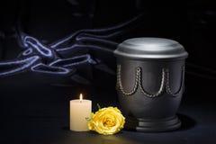 有灼烧的蜡烛黄色玫瑰的黑公墓缸在深刻的蓝色背景 库存图片