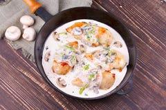 有炸鸡乳房、蘑菇和绿色的煎锅 免版税库存图片