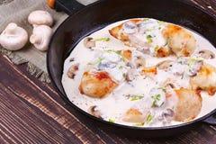有炸鸡乳房、蘑菇和绿色的煎锅 库存照片