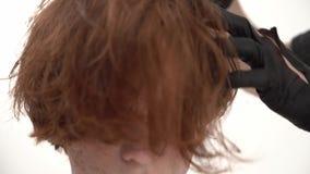 有烘干和称呼他的客户的姜头发的hairdryer的理发师 股票录像