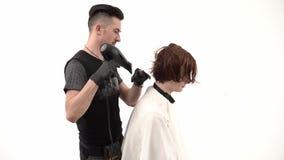 有烘干和称呼他的客户的姜头发的hairdryer的理发师 股票视频