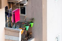 有烘干挂衣架,花盆的衣裳的局促公寓阳台 免版税图库摄影