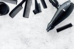 有烘干机和工具的美发师运转的书桌为称呼在灰色石书桌背景顶视图嘲笑的头发  免版税图库摄影