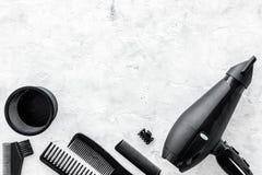 有烘干机和工具的美发师运转的书桌为称呼在灰色石书桌背景顶视图嘲笑的头发  免版税库存图片