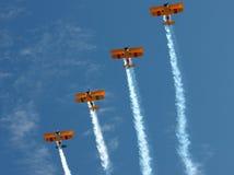 有烟上升的四架双翼飞机 图库摄影
