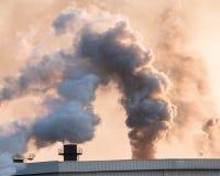 有烟和污染的在天空,全球性战争工厂灼烧的藤茎 图库摄影