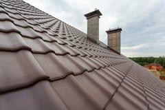 有烟囱、自然红色瓦片和烟囱的屋顶 免版税库存照片