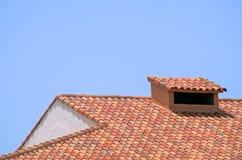有烟囱的铺磁砖的屋顶 免版税库存图片