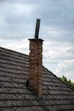 有烟囱的年迈的瓦在老房子在村庄 在小屋铺磁砖的屋顶的很多青苔反对蓝色多云天空的 乡下 库存图片