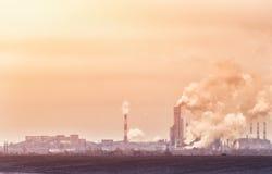 有烟的工厂从在黄色和橙色口气的管子肮脏的被污染的工业区 免版税库存照片