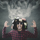 有烟的沮丧的蓬松卷发人在头 图库摄影