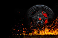 有烟的漂移的在黑背景隔绝的车轮和火 库存图片