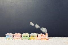 有烟的被盖的活动火车玩具在黑板ba的雪 库存图片