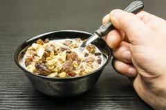 有烤嘎吱咬嚼的可可粉muesli的快的健康早餐碗用花生、牛奶巧克力、焦糖和葡萄干用牛奶 图库摄影