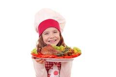 有烤火鸡鼓槌的小女孩厨师 库存照片