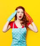 有烤箱手套和围裙的女孩 免版税库存图片