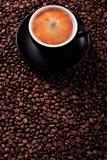 有烤豆背景垂直copyspace的无奶咖啡杯子 免版税库存照片