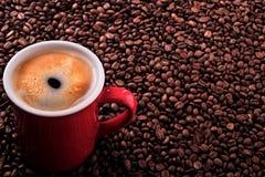 有烤豆背景拷贝空间的红色咖啡杯 免版税库存图片