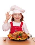 有烤鸡的小女孩厨师 库存图片
