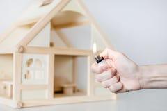 有烧的手轻反对在背景的木房子模型 房子概念放火  犯罪事故 免版税库存照片
