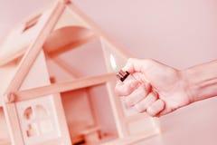 有烧的手轻反对在背景的木房子模型 房子概念放火  犯罪事故 免版税库存图片