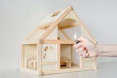 有烧的手轻反对在背景的木房子模型 房子概念放火  犯罪事故 免版税图库摄影