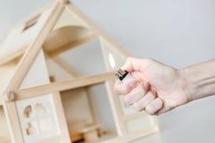 有烧的手轻反对在背景的木房子模型 房子概念放火  犯罪事故 库存图片