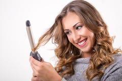 有烫发钳的美丽的妇女 免版税库存照片