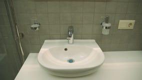 有热和冷的龙头的陶瓷水盆在豪华旅馆卫生间里 库存照片