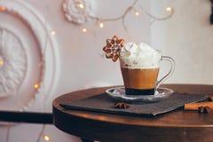 有热奶咖啡的一个杯子在木桌上的圣诞灯背景 免版税库存照片