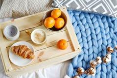 有热奶咖啡的,新月形面包,蓝色淡色巨型格子花呢披肩,卧室,早晨概念杯 库存照片