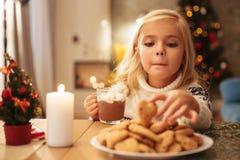 有热巧克力采取饼干从的杯子的滑稽的小女孩 免版税库存图片