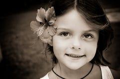 有热带花的小女孩在她的头发 免版税库存照片