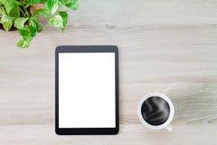 有热的咖啡杯和绿色植物罐的空白的白色屏幕片剂计算机在木书桌上 免版税库存图片