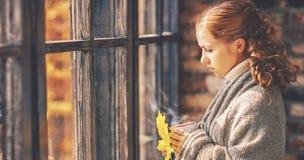 有热的咖啡杯的哀伤的少妇在秋天窗口里 免版税库存照片