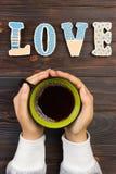 有热的咖啡的妇女,用饼干 概念亲吻妇女的爱人 爱词用咖啡 免版税库存照片
