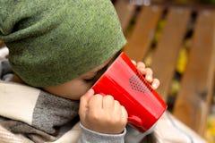 有热的杯子的男孩茶 免版税图库摄影