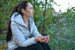 有热的茶坐在森林里和享受自然的杯子的妇女远足者 免版税库存照片